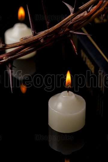 Close up of the crown of thorns and Bible in lights of candles