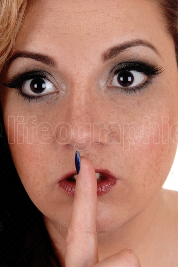 Close up of the face of a woman with finger over mouth