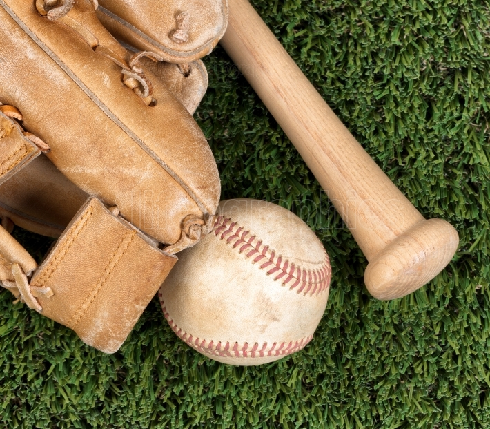 Close up overhead view of old baseball equipment on grass