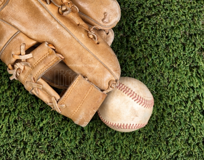 Close up overhead view of old leather baseball and mitt on grass