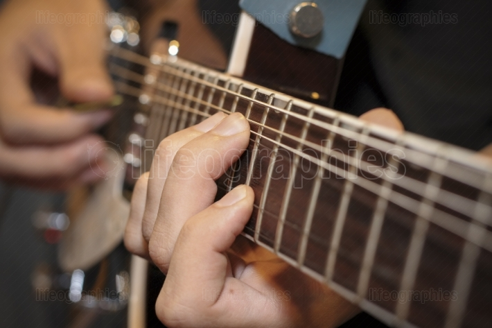 Close up shot of a man with his fingers on the frets of a guitar