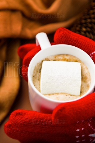Close up view of person with red gloves taking a cup of hot choc