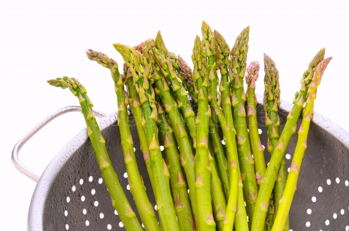 Closeup asparagus in colander isolated