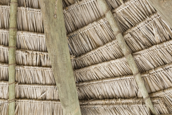 Close-up of hanging edge of thatched umbrellas on beach