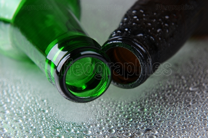 Closeup of two beer bottles on Wet Surface