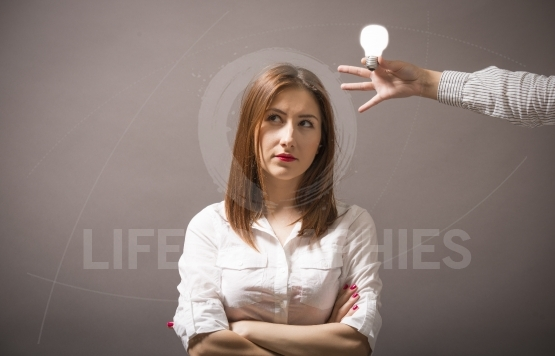 Closeup portrait beautiful woman thinks and bright light bulb