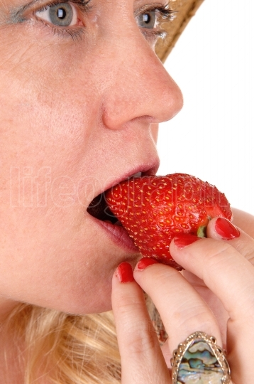 Closeup woman eating strawberry.