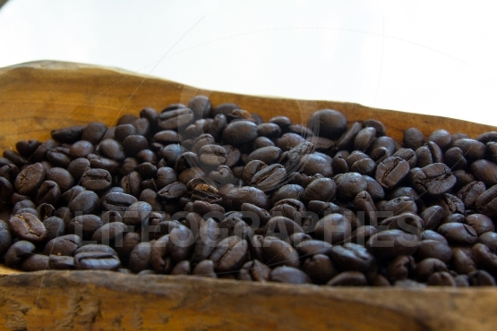 Coffee beans in a wooden bowls on white background