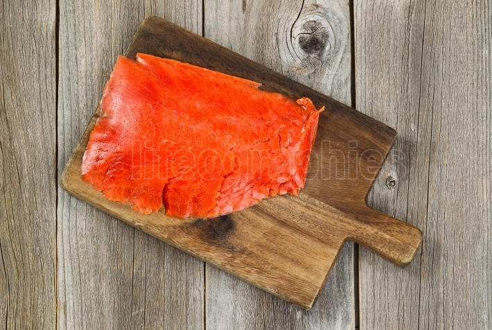 Cold Smoked Red Salmon on wooden server board with rustic wood b