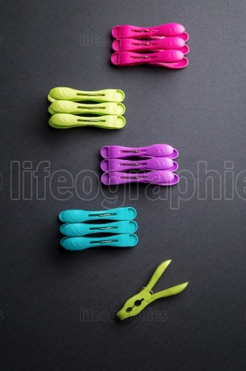 Colored laundry clips over a black background above view