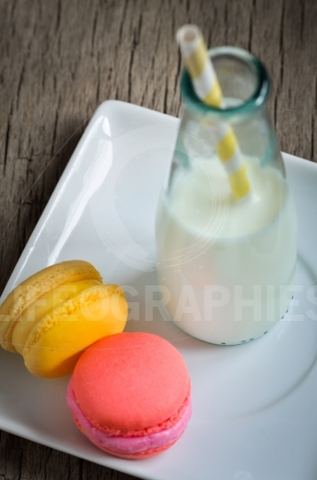 Colorful macaroons and milk in a bottle with striped straws
