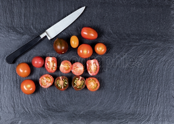 Colorful mixed small tomatoes and cutting knife on natural black