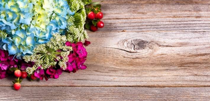Colorful seasonal assorted flowers on stressed wood background