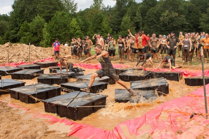 Competitors run across floating platforms at extreme obstacle co