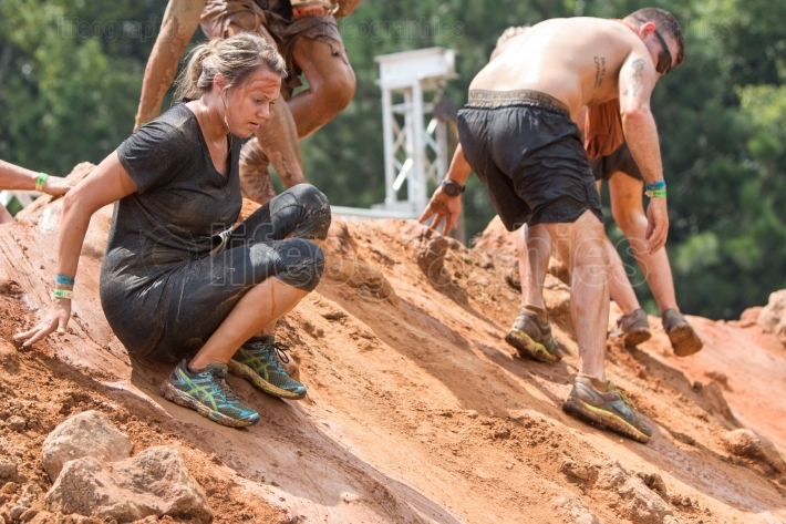 Competitors slide down slippery hill at extreme obstacle course