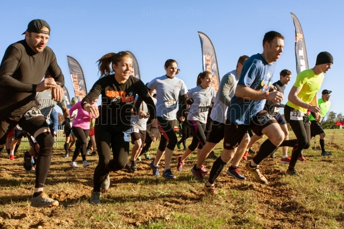 Competitors sprint from start line at obstacle course race