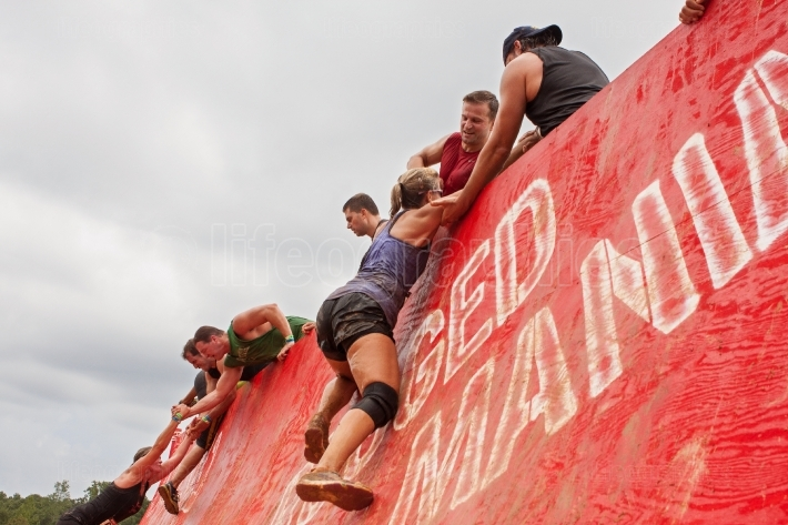 Competitors struggle to climb wall in extreme obstacle course ra