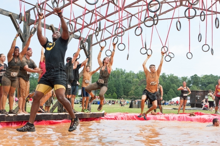 Competitors swing from rings over water at extreme obstacle cour