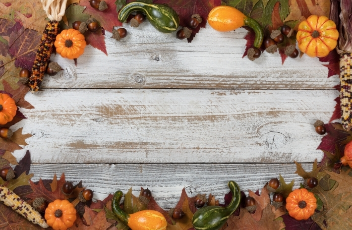 Complete circle border of Autumn foliage with other fall decorations on white rustic wood