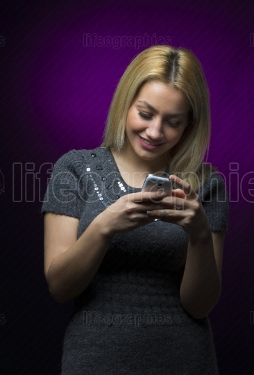 Concentrated blonde haired model holding smartphone on black background