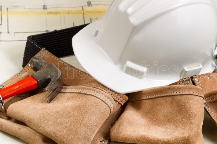 Construction contractor tools with blue print drawings in backgr