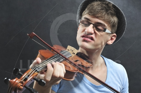 Cool young boy with sunglasses playing violin