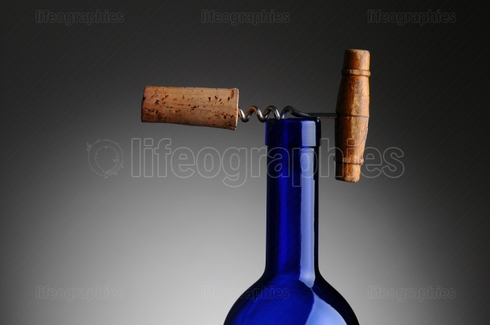 Corkscrew and Cork on Top of Wine Bottle