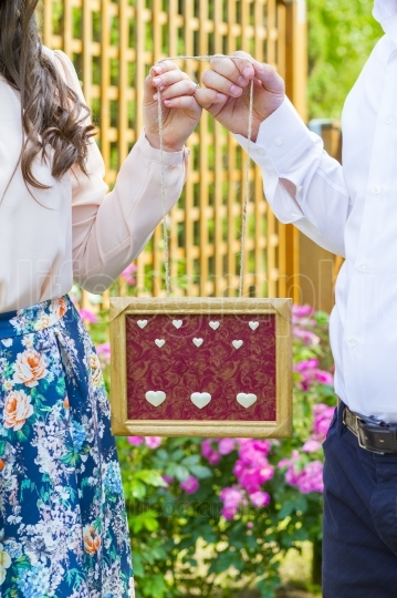 Couple holding wooden frame in hands