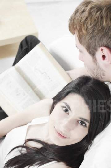 Couple reading book on a sofa