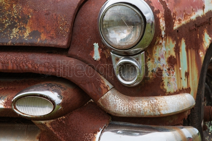 Cracked Headlight And Chipped Paint On Old Rusted Junkyard Car