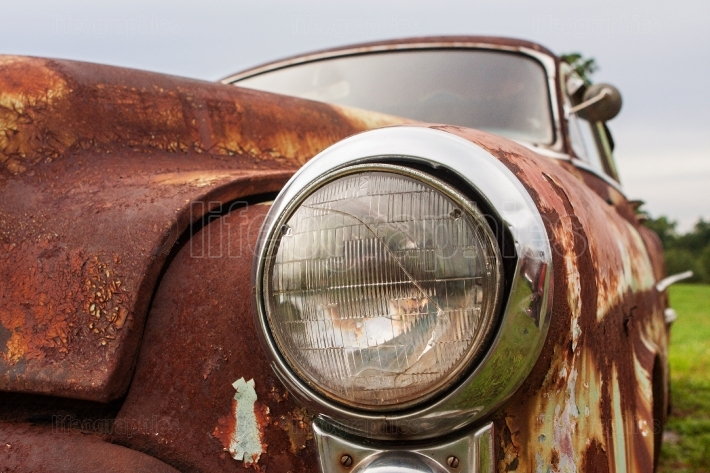 Cracked Headlight On Old Rusted Junkyard Car