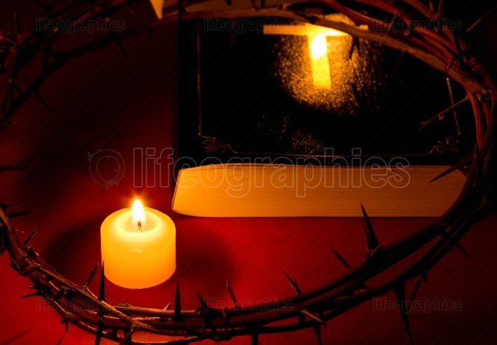Crown of Thorns of Jesus Christ put on the Bible beside a candle