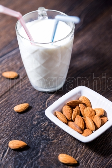 Cup of almond milk with drinking straws and nuts on table
