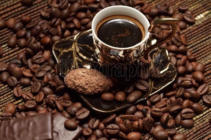Cup of coffee with grains and chocolate