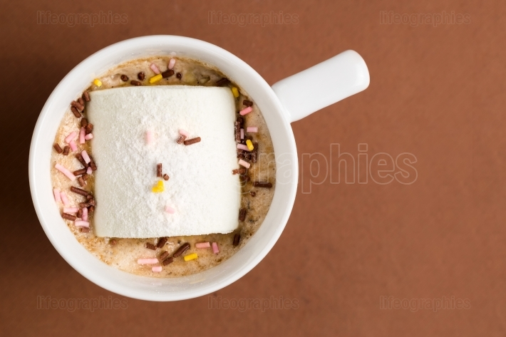Cup of hot cocoa with marshmallow on brown background