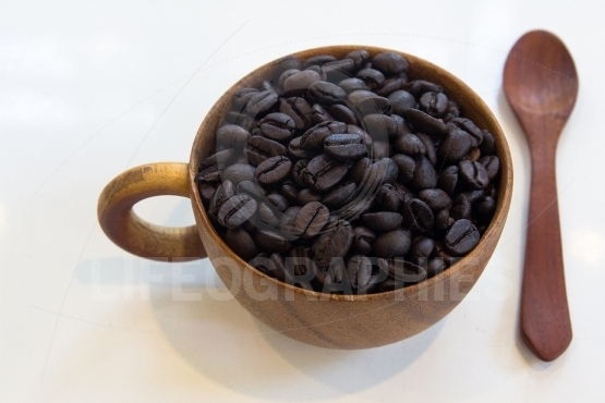 Cup with coffee beans isolated on  table background