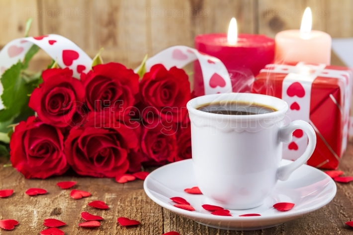 Cup with coffee in front of bouquet of red roses
