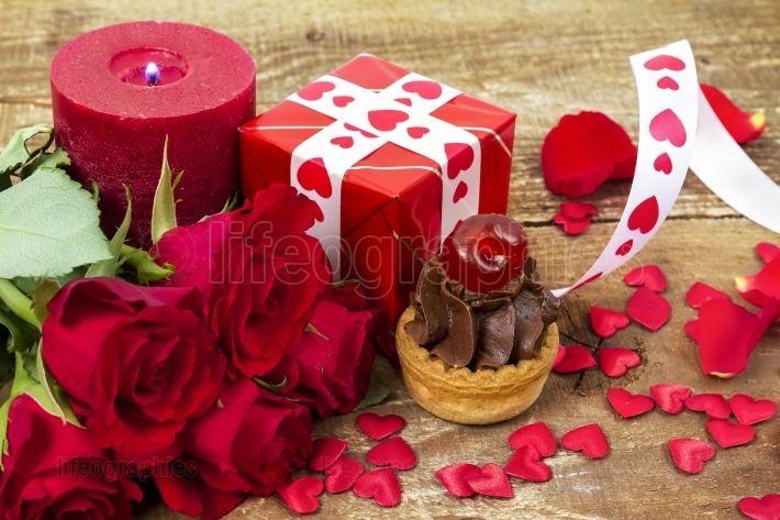 Cupcake with cherry in front of bouquet of red roses