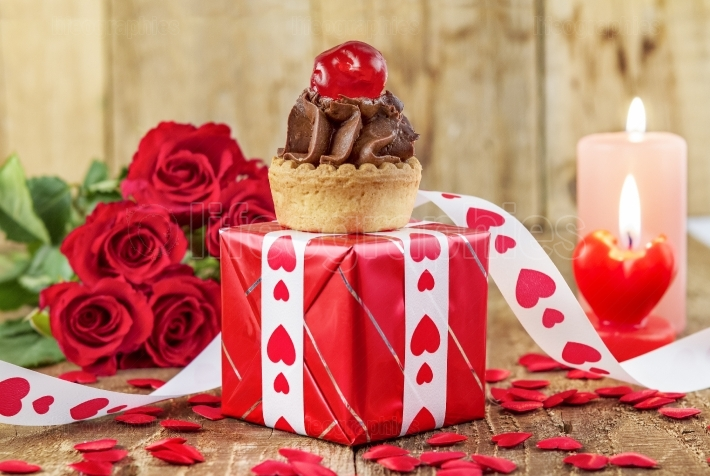 Cupcake with cherry over red gift box