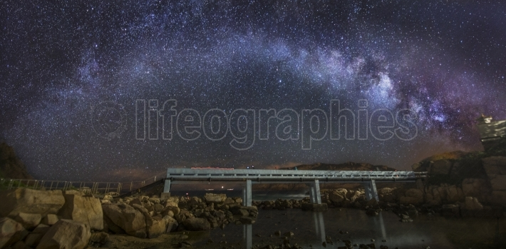 Curved Milky Way over a bridge