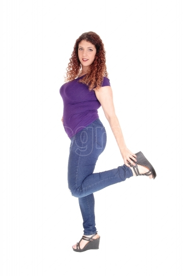 Curvy woman standing in profile with leg up