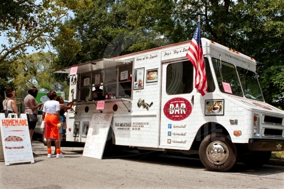 Customers order meals from food truck in park