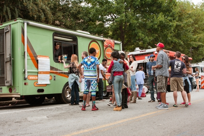 Customers stand in line to buy meals from food trucks