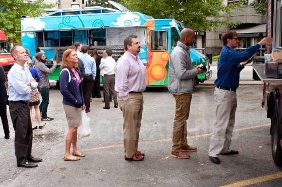Customers stand in line to order meals from food trucks