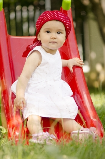 Cute baby girl playing on slide