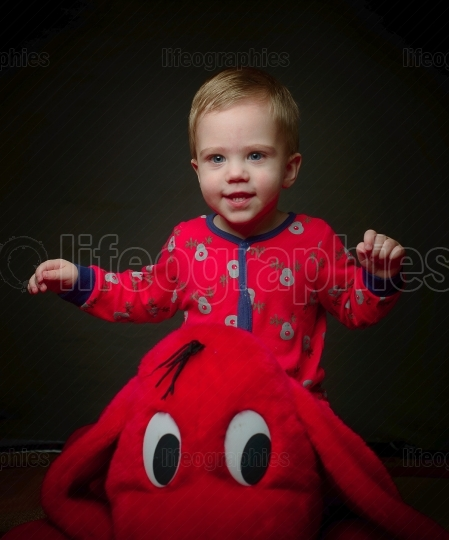 Cute blonde little boy in red with his toy