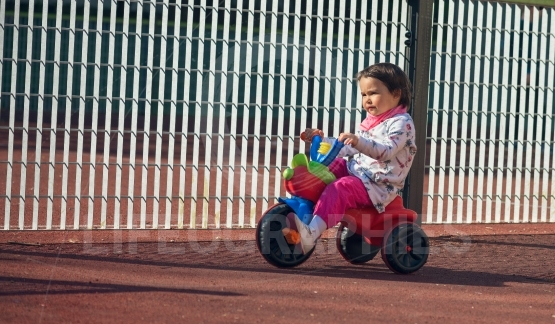 Cute three-year-old little child riding a 3-wheel bike in playground