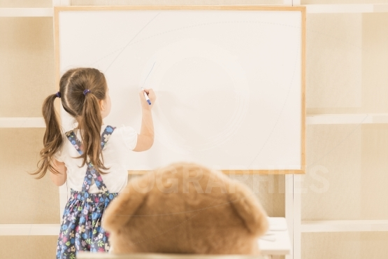 Cute toddler playing teacher role game with her toy