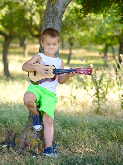 Cute young boy playing guitar near the summer tree