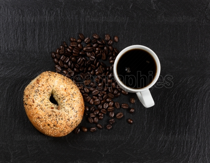 Dark coffee and bagel with roasted beans on natural slate stone